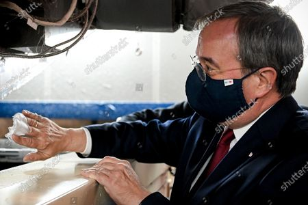 Stock Image of Prime Minister of North Rhine-Westphalia Armin Laschet dips his fingers in meltblown nonwovens as he visits the production facility of Innovatec Microfibre Technology, amid the on-going Covid-19 pandemic, in Troisdorf, Germany, 20 November 2020. The occasion was the commissioning of the first of three new lines for the production of meltblown nonwovens. Meltblown is the heart of every medical protective mask and is urgently needed in the current corona crisis worldwide for the production of surgical and FFP masks. Countries around the world are taking increased measures to stem the widespread of the SARS-CoV-2 coronavirus which causes the COVID-19 disease.