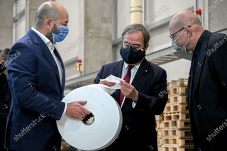 Prime Minister of North Rhine-Westphalia Armin Laschet (C) handles a roll of meltblown nonwovens as he visits the production facility of Innovatec Microfibre Technology, amid the on-going Covid-19 pandemic, in Troisdorf, Germany, 20 November 2020. The occasion was the commissioning of the first of three new lines for the production of meltblown nonwovens. Meltblown is the heart of every medical protective mask and is urgently needed in the current corona crisis worldwide for the production of surgical and FFP masks. Countries around the world are taking increased measures to stem the widespread of the SARS-CoV-2 coronavirus which causes the COVID-19 disease.
