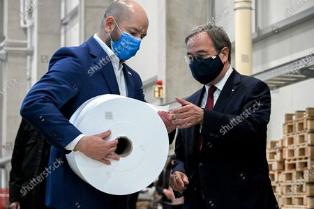 Prime Minister of North Rhine-Westphalia Armin Laschet (R) handles a roll of meltblown nonwovens as he visits the production facility of Innovatec Microfibre Technology, amid the on-going Covid-19 pandemic, in Troisdorf, Germany, 20 November 2020. The occasion was the commissioning of the first of three new lines for the production of meltblown nonwovens. Meltblown is the heart of every medical protective mask and is urgently needed in the current corona crisis worldwide for the production of surgical and FFP masks. Countries around the world are taking increased measures to stem the widespread of the SARS-CoV-2 coronavirus which causes the COVID-19 disease.