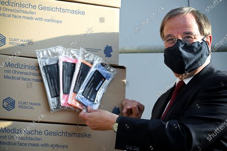Stock Picture of Prime Minister of North Rhine-Westphalia Armin Laschet shows medical face masks as he visits the production facility of Innovatec Microfibre Technology, amid the on-going Covid-19 pandemic, in Troisdorf, Germany, 20 November 2020. The occasion was the commissioning of the first of three new lines for the production of meltblown nonwovens. Meltblown is the heart of every medical protective mask and is urgently needed in the current corona crisis worldwide for the production of surgical and FFP masks. Countries around the world are taking increased measures to stem the widespread of the SARS-CoV-2 coronavirus which causes the COVID-19 disease.