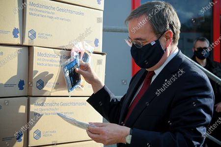 Prime Minister of North Rhine-Westphalia Armin Laschet inspects medical face masks as he visits the production facility of Innovatec Microfibre Technology, amid the on-going Covid-19 pandemic, in Troisdorf, Germany, 20 November 2020. The occasion was the commissioning of the first of three new lines for the production of meltblown nonwovens. Meltblown is the heart of every medical protective mask and is urgently needed in the current corona crisis worldwide for the production of surgical and FFP masks. Countries around the world are taking increased measures to stem the widespread of the SARS-CoV-2 coronavirus which causes the COVID-19 disease.