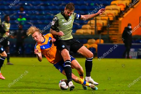 George Lapslie of Mansfield Town collides with Harry Pell of Colchester United