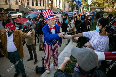 A man dressed as Uncle Sam along with a a large gathering of Trump supporters argue with a group of Biden supporters outside the Georgia Capitol Building on Wednesday, Nov. 18, 2020 in Atlanta, GA. (Jason Armond / Los Angeles Times)