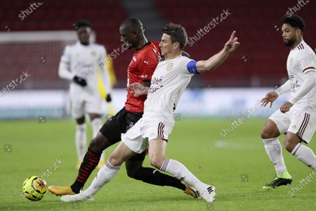 Rennes' Serhou Guirassy, left, fights for the ball with Bordeaux's Laurent Koscielny during the League One soccer match between Rennes and Bordeaux, at the Roazhon Park stadium in Rennes, France
