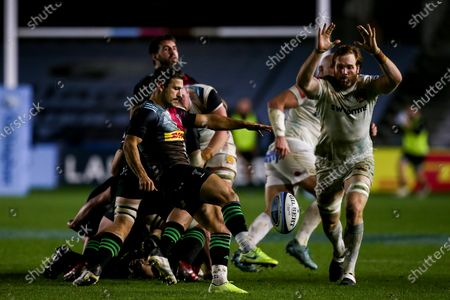 Danny Care of Harlequins kicks under pressure from Jannes Kirsten of Exeter Chiefs