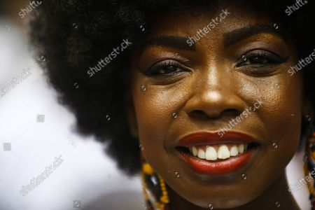 Member of the Mocidade Unida do Santa Marta samba school smiles for a portrait as she attends a ceremony marking Black Consciousness Day in the Santa Marta favela of Rio de Janeiro, Brazil, . Brazilians celebrate the holiday with Afro-Brazilian dance, music and religious ceremonies, reflecting the deep cultural and social ties of the Black community to the country's history and honor legendary anti-slave leader Zumbi dos Palmares on the day of his death