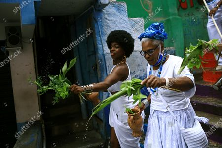 """Members of the Mocidade Unida do Santa Marta samba school perform a washing ritual for good luck called """"Lavagem"""" as they attend a ceremony marking Black Consciousness Day in the Santa Marta favela of Rio de Janeiro, Brazil, . Brazilians celebrate the holiday with Afro-Brazilian dance, music and religious ceremonies, reflecting the deep cultural and social ties of the Black community to the country's history and honor legendary anti-slave leader Zumbi dos Palmares on the day of his death"""