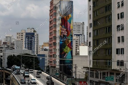 A graffiti by the Brazilian street artist Eduardo Kobra on a 33-meter-high building depicts a divine hand rescuing a human hand, in Sao Paulo, Brazil, 14 November 2020 (issued 20 November 2020). During an interview with Spanish international news agency Efe, Kobra, 45, said, 'I realized that if I stop painting, my death is imminent.' The artist spoke about his relationship with art and his new, most 'autobiographical' work, which he created when morning the loss of his newborn child just hours after birth as the coronavirus Covid-19 pandemic emergency began.