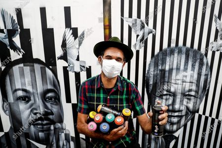 Brazilian street artist Eduardo Kobra poses in front of one of his artworks, which depicts Martin Luther King Jr. (L) and Nelson Mandela, after an interview with Spanish international news agency Efe at his workshop in Sao Paulo, Brazil, 19 November 2020 (issued 20 November 2020). During the interview, Kobra, 45, said, 'I realized that if I stop painting, my death is imminent.' The artist spoke about his relationship with art and his new, most 'autobiographical' work, which he created when morning the loss of his newborn child just hours after birth as the coronavirus Covid-19 pandemic emergency began.