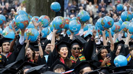 Graduates of Harvard's John F. Kennedy School of Government hold aloft inflatable globes as they celebrate graduating during Harvard University's commencement exercises in Cambridge, Mass. A petition circulating at Harvard University demands that school officials create new accountability standards for former Trump administration officials who seek to work or speak on campus, an idea that has drawn outrage from prominent conservatives