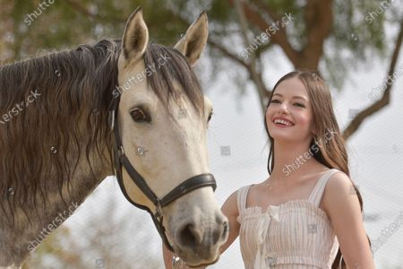 """Mackenzie Foy poses with Director Ashley Avis's horse Ghost at an event to promote the film """"Black Beauty"""" at Fair Hill Farms, in Topanga, Calif"""