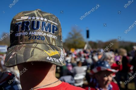 A supporter of President Trump wears a MAGA hat before Vice President Mike Pence speaks at a campaign rally with Senators Kelly Loeffler and David Perdue before leaving.