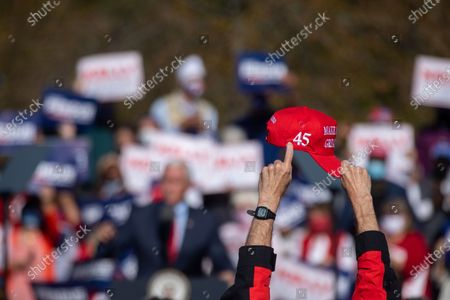 "A supporter of President Trump holds up a MAGA hat while pointing at ""45"" as Vice President Mike Pence speaks at a campaign rally with Senators Kelly Loeffler and David Perdue before leaving."