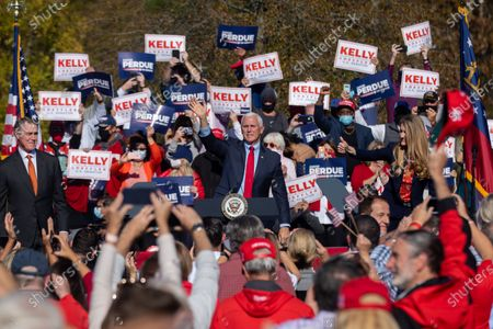 Vice President Mike Pence waves at a campaign rally with Senators David Perdue and Kelly Loeffler before leaving.