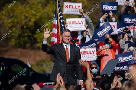 Senator David Perdue waves at a campaign rally with Senator Kelly Loeffler and Vice President Mike Pence before leaving.