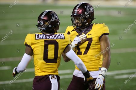 Minnesota wide receiver Seth Green (17) smiles at wide receiver Rashod Bateman (0) after Green scored a touchdown during the first half of the team's NCAA college football game against Purdue, in Minneapolis