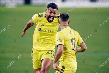 Stock Picture of Nashville SC midfielder Anibal Godoy (20) celebrates with forward Randall Leal (8) after Leal scored a goal against Inter Miami during the first half of an MLS soccer playoff match, in Nashville, Tenn
