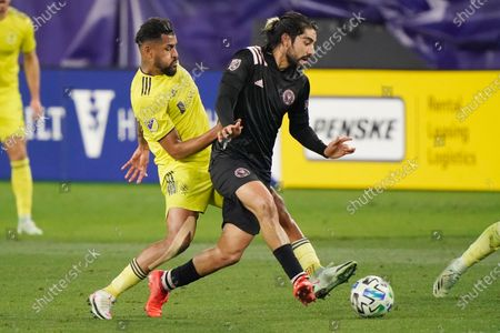 Stock Image of Nashville SC midfielder Anibal Godoy, left, and Inter Miami midfielder Rodolfo Pizarro, right, battle for the ball during the first half of an MLS soccer playoff match, in Nashville, Tenn