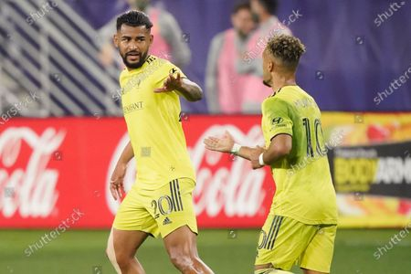 Nashville SC's Anibal Godoy (20) congratulates midfielder Hany Mukhtar (10) after Mukhtar scored a goal against Inter Miami during the first half of an MLS soccer playoff match, in Nashville, Tenn