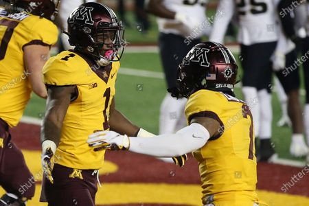 Minnesota wide receiver Chris Autman-Bell (7) high fives Minnesota running back Cam Wiley (1) after Wiley scored a touchdown during the first half of an NCAA college football game, in Minneapolis. Minnesota won 34-31
