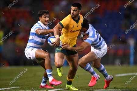 Stock Picture of Tom Wright of the Wallabies offloads a pass as he is tackled by Emiliano Boffelli (right) and Santiago Carreras of the Pumas during the Tri Nations rugby match between the Argentina Pumas and Australian Wallabies at McDonald Jones Stadium in Newcastle, 21 November 2020.