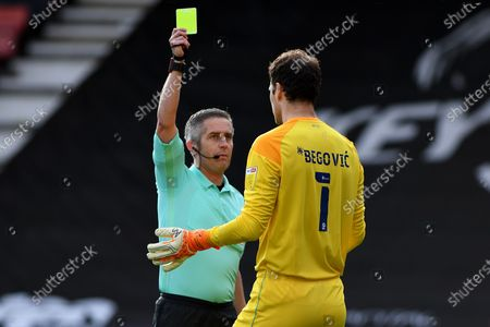 Referee Darren Bond shows Asmir Begovic of AFC Bournemouth a yellow card after a foul leading to a penalty - AFC Bournemouth v Reading, Sky Bet Championship, Vitality Stadium, Bournemouth, UK - 21st November 2020Editorial Use Only - DataCo restrictions apply