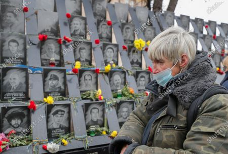 Stock Image of Ukrainians lay flowers at the memorial for Maidan activists or 'Heroes of the Heavenly Hundred', who were killed on the Maidan during anti-government protests in 2014, not far from Independence Square, amid the coronavirus COVID-19 pandemic, in Kiev, Ukraine, 21 November 2020. Ukrainians marked the anniversary of the Euromaidan revolution, commemorating 21 November 2013, on which activists started an anti-government picket after then-Prime Minister Mykola Azarov announced the suspension of a landmark treaty with the European Union. The protests eventually led to the ouster of President Viktor Yanukovych, creating political rifts through the country that erupted into a violent conflict between separatists and government forces in the eastern part of the country in the spring.