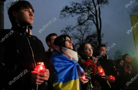 Ukrainians hold candles at the memorial for Maidan activists or 'Heroes of the Heavenly Hundred', who were killed on the Maidan during anti-government protests in 2014, not far from Independence Square in Kiev, Ukraine, 21 November 2020. Ukrainians marked the anniversary of the Euromaidan revolution, commemorating 21 November 2013, on which activists started an anti-government picket after then-Prime Minister Mykola Azarov announced the suspension of a landmark treaty with the European Union. The protests eventually led to the ouster of President Viktor Yanukovych, creating political rifts through the country that erupted into a violent conflict between separatists and government forces in the eastern part of the country in the spring.