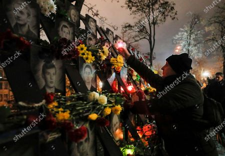 Stock Picture of Ukrainians light candles at the memorial for Maidan activists or 'Heroes of the Heavenly Hundred', who were killed on the Maidan during anti-government protests in 2014, not far from Independence Square in Kiev, Ukraine, 21 November 2020. Ukrainians marked the anniversary of the Euromaidan revolution, commemorating 21 November 2013, on which activists started an anti-government picket after then-Prime Minister Mykola Azarov announced the suspension of a landmark treaty with the European Union. The protests eventually led to the ouster of President Viktor Yanukovych, creating political rifts through the country that erupted into a violent conflict between separatists and government forces in the eastern part of the country in the spring.