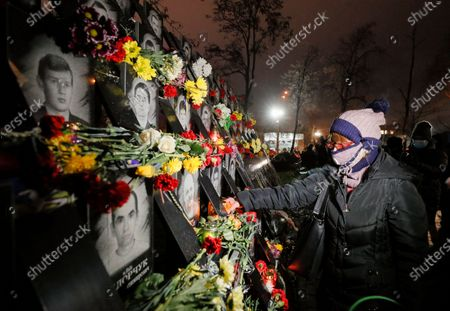 Stock Photo of Ukrainians light candles and lay flowers at the memorial for Maidan activists or 'Heroes of the Heavenly Hundred', who were killed on the Maidan during anti-government protests in 2014, not far from Independence Square in Kiev, Ukraine, 21 November 2020. Ukrainians marked the anniversary of the Euromaidan revolution, commemorating 21 November 2013, on which activists started an anti-government picket after then-Prime Minister Mykola Azarov announced the suspension of a landmark treaty with the European Union. The protests eventually led to the ouster of President Viktor Yanukovych, creating political rifts through the country that erupted into a violent conflict between separatists and government forces in the eastern part of the country in the spring.