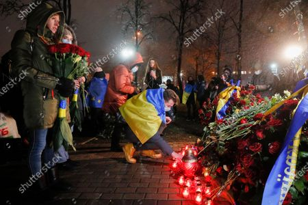Ukrainians light candles at the memorial for Maidan activists or 'Heroes of the Heavenly Hundred', who were killed on the Maidan during anti-government protests in 2014, not far from Independence Square in Kiev, Ukraine, 21 November 2020. Ukrainians marked the anniversary of the Euromaidan revolution, commemorating 21 November 2013, on which activists started an anti-government picket after then-Prime Minister Mykola Azarov announced the suspension of a landmark treaty with the European Union. The protests eventually led to the ouster of President Viktor Yanukovych, creating political rifts through the country that erupted into a violent conflict between separatists and government forces in the eastern part of the country in the spring.