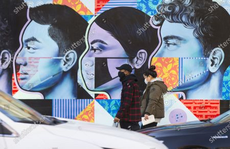 People wearing face masks walk past a mural in Toronto, Canada, on Nov. 20, 2020. Canadian Prime Minister Justin Trudeau said on Friday that the country is at stake as COVID-19 has been worsening. As of Friday afternoon, Canada reported a total of 319,038 cases and 11,313 deaths.