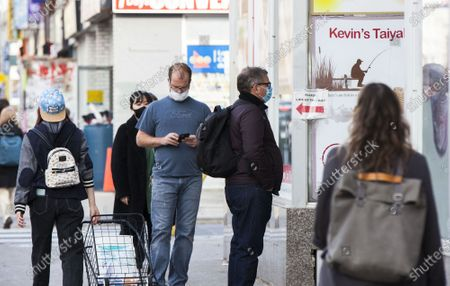 Stock Image of People wearing face masks line up to enter a supermarket in Toronto, Canada, on Nov. 20, 2020. Canadian Prime Minister Justin Trudeau said on Friday that the country is at stake as COVID-19 has been worsening. As of Friday afternoon, Canada reported a total of 319,038 cases and 11,313 deaths.