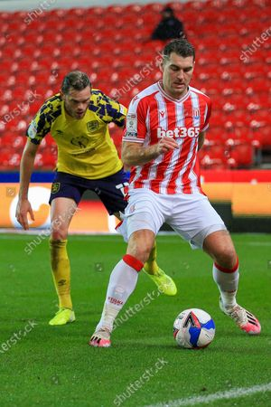 Sam Vokes (9) of Stoke City  holds off a challenge for the ball from Richard Stearman of Huddersfield Town (12) during the EFL Sky Bet Championship match between Stoke City and Huddersfield Town at the Bet365 Stadium, Stoke-on-Trent