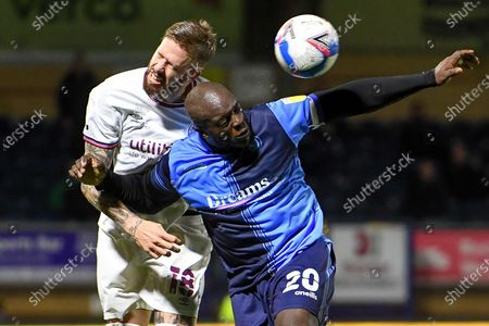 Brentford FC defender Pontus Jansson (18) heads the ball under pressure from Wycombe Wanderers striker Adebayo Akinfenwa (20) during the EFL Sky Bet Championship match between Wycombe Wanderers and Brentford at Adams Park, High Wycombe