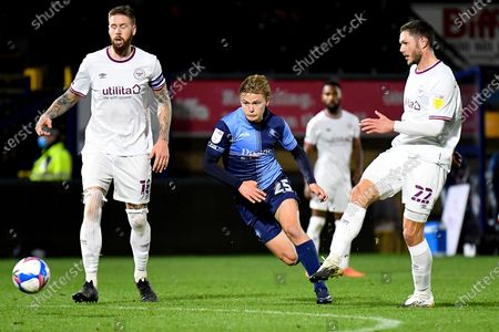 Wycombe Wanderers striker Alex Samuel (25) bursts between Brentford FC defender Pontus Jansson (18) and Brentford FC defender Henrik Dalsgaard (22) during the EFL Sky Bet Championship match between Wycombe Wanderers and Brentford at Adams Park, High Wycombe