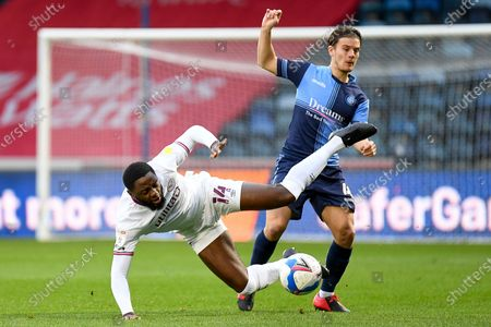 Brentford FC midfielder Josh Dasilva (14) takes a tumble in a clash with Wycombe Wanderers midfielder Dominic Gape (4) during the EFL Sky Bet Championship match between Wycombe Wanderers and Brentford at Adams Park, High Wycombe