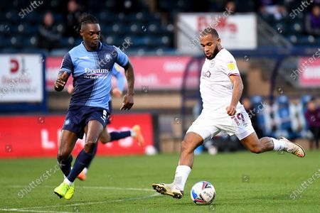Brentford FC midfielder Bryan Mbeumo (19) takes a shot at goal and hits the post under pressure from Wycombe Wanderers defender Anthony Stewart (5) during the EFL Sky Bet Championship match between Wycombe Wanderers and Brentford at Adams Park, High Wycombe