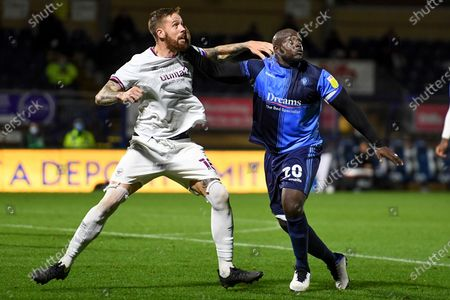 Stock Image of Wycombe Wanderers striker Adebayo Akinfenwa (20) battles for possession  with Brentford FC defender Pontus Jansson (18) during the EFL Sky Bet Championship match between Wycombe Wanderers and Brentford at Adams Park, High Wycombe