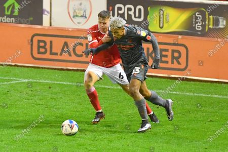 Stock Image of Barnsley FC player Mads Juel Andersen (6) and Nottingham Forest Forward Lyle Taylor (33) during the EFL Sky Bet Championship match between Barnsley and Nottingham Forest at Oakwell, Barnsley