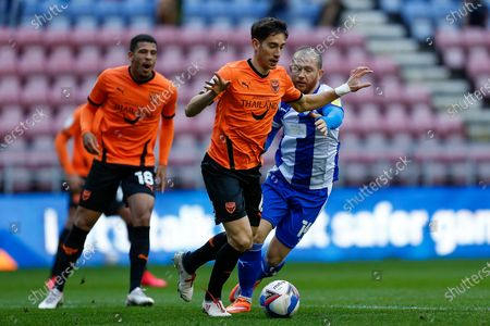 Stock Picture of Wigan Athletic FC Forward and Captain Joe Garner (14) runs after Oxford United FC Midfielder Alex Rodriguez Gorrin (6) during the EFL Sky Bet League 1 match between Wigan Athletic and Oxford United at the DW Stadium, Wigan