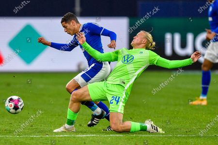 Schalke's Salif Sane, duels for the ball with Wolfsburg's Xaver Schlager, foreground, during the German Bundesliga soccer match between VfL Wolfsburg and FC Schalke 04 at the Veltins-Arena in Gelsenkirchen, Germany