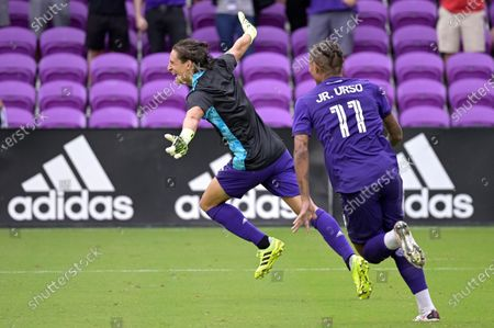 Orlando City defender Rodrigo Schlegel, left, celebrates after blocking the final New York City FC penalty kick during overtime of an MLS soccer playoff match, in Orlando, Fla. Schlegal was sent in to substitute for goalkeeper Pedro Gallese who was ejected after getting his second yellow card