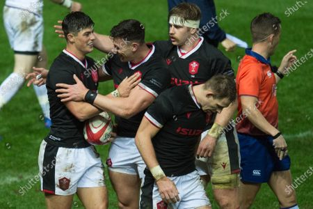 Louis Rees-Zammit of Wales celebrates his try with Johnny Williams of Wales and Aaron Wainwright of Wales