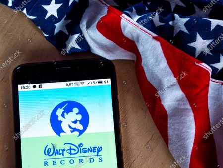 In this photo illustration a Walt Disney Records logo seen displayed on a smartphone with the US flag in the background.