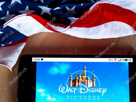 Stock Image of In this photo illustration a Walt Disney Records logo seen displayed on a smartphone with the US flag in the background.