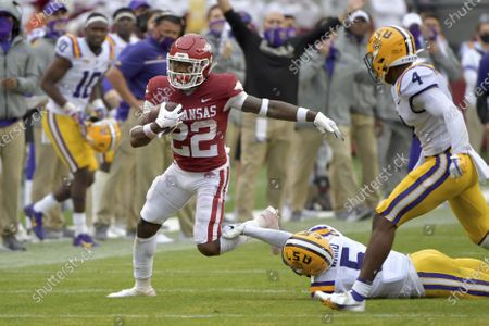 Arkansas running back Trelon Smith (22) slips past LSU defenders Jay Ward (5) and Todd Harris Jr. (4) as he runs the ball during the second half of an NCAA college football game, in Fayetteville, Ark