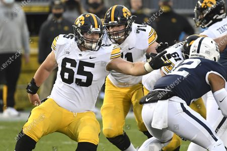 Iowa offensive lineman Tyler Linderbaum (65) looks to block Penn State linebacker Brandon Smith (12) in the first quarter of an NCAA college football game in State College, Pa., on