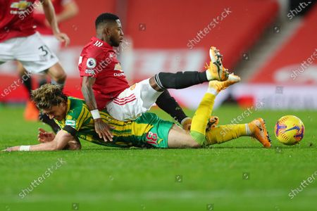 Manchester United's Fred, center, and West Bromwich Albion's Conor Gallagher, low, fight for the ball during the English Premier League soccer match between Manchester United and West Bromwich Albion at the Old Trafford stadium in Manchester, England