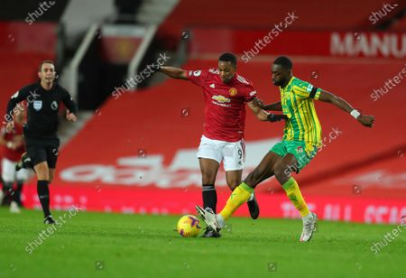 Manchester United's Anthony Martial and West Bromwich Albion's Semi Ajayi, right, fight for the ball during the English Premier League soccer match between Manchester United and West Bromwich Albion at the Old Trafford stadium in Manchester, England